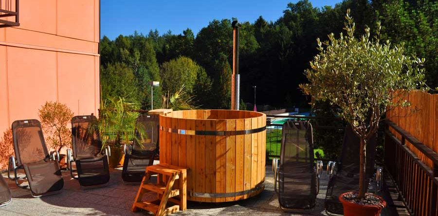 pic Wood-fired Hot Tub flexibility and possibility to use it in any seasons allow considering the tub as a challenging option of a vitality pool or jacuzzi. On top of that, a small company will find this tub to be great fun. These tubs are made of wood, which has passed a special heat-treatment process. It gives good resistance to weather conditions and precipitation. Over the years, wooden products retain their original appearance, however, the problem of care and tightness is easier and more reliable to solve in a seamless design. It is worth considering the size and shape of the wood-fired hot tub, because the product should definitely fit the overall recreation interior and the place to take hydrotherapeutic procedures. They should be comfortable, functional and aesthetic. The Wood-fired Hot Tub size directly depends on its shape and standard parameters. In addition, there are tubs for two, three, four and more people. Depending on where you are going to arrange the wood-fired hot tub and how many people will use it at the same time, it is possible to choose these or those parameters. When choosing a wood-fired hot tub, pay attention to product dimensions: length width height For example, a two-person Wood-fired Hot Tub can be from 100 cm in diameter for oval models. The length of round Wood-fired Hot Tub is from 160 cm and more. Take into account, if the average height of a Wood-fired Hot Tub is 120 cm, its useful height from the bottom will make 110 cm, as the wood-fired hot tub bottom (because of natural ventilation and installation of drain communications) is placed approximately 10 cm from the floor. You can combine the beauty of wood texture and absolute water resistance in a combined design. Its outer part consists of wooden slats, like a classic Wooden Hot Tub. Inside the wooden tub is installed a liner made of fiberglass, which does not require special care, unlike wood. The Wood-fired Hot Tub is most often made in geometric forms; it may be rectangular, octagonal, round or oval shape. The size and shape of the Wood-fired Hot Tub determine the capacity and speed of water heating. Heating water in the Wood-fired Hot Tubs with a Wood-burning stove is the most popular type. This is a simple and economical option and quite coincides with the majority of people about the right rest. Water heats up quickly (1-3 hours depending on the volume of the wood-fired hot tub, and the power of the furnace used). This is very important in regions with cold climates. If you do not know which shape of the Wood-fired Hot Tub to choose, how to calculate its size, color and material, we recommend you to contact our sales team. We will be glad to help choose the best model customized for your space and place of further use.